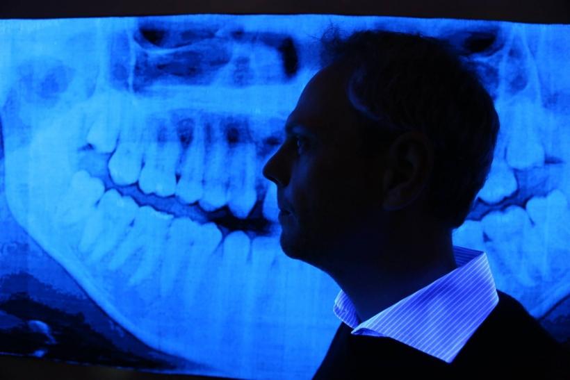 Durch Sehschlitze blicken sie auf leuchtende Röntgenaufnahmen von Kieferknochen. Das ansonsten schlichte Schwarz-Weiß-Objekt wirkt erst durch den Einsatz von Schwarzlicht. Es lässt fluoreszierende Angelschnur bläulich leuchten (Foto: