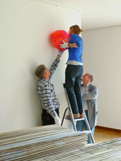 """Ausstellungsaufbau """"Living in the material World"""": Die künstlerin Berta Fischer hängt ihre Skulptur """"Ems"""" auf. (Foto: Kunstmuseen Krefeld, Sylvia Martin)"""