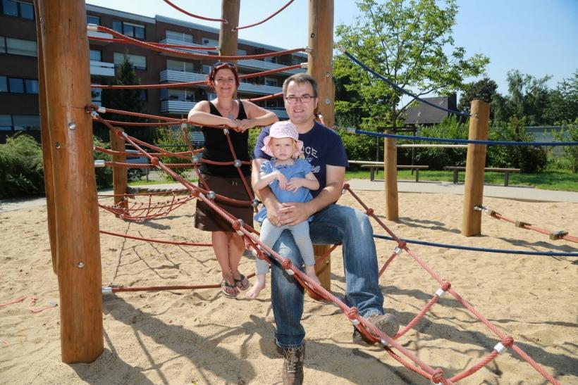 """Spielplatzpatin Christiane van Bracht und Pate Christian Kölbl (mit Töchterchen Lena) sind sehr zufrieden mit dem Angebot auf """"ihrem"""" Spielplatz am Plankerdyk. (Foto: Lothar Strücken)"""