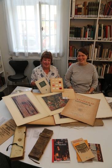 Marion Porsch (links) und Museumsleiterin Dr. Annette Schieck zeigen Schätze aus der Bibliothek des Textilmuseums: Porsch präsentiert das 10 000. Buch der Sammlung: ein Musterbuch für Weber mit Stoffproben. (Foto: Lothar Strücken)