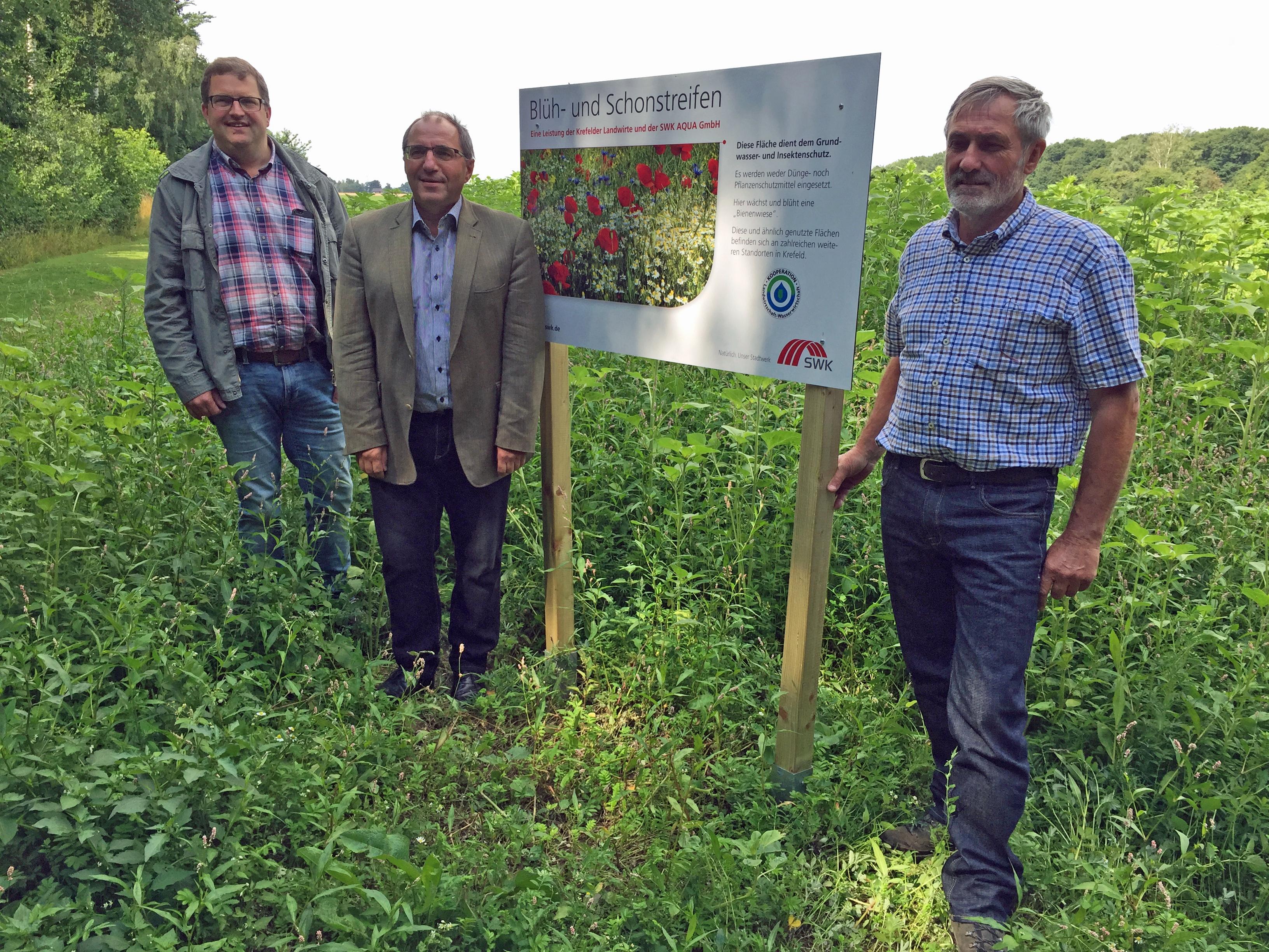 Landwirt Thomas Vennekel, Michael Rögele, Geschäftsführer der SWK Aqua und Landwirt Heinz-Albert Schmitz am Blühstreifen am Forstwald.  (Foto: Stadt Krefeld, Presse und Kommunikation)
