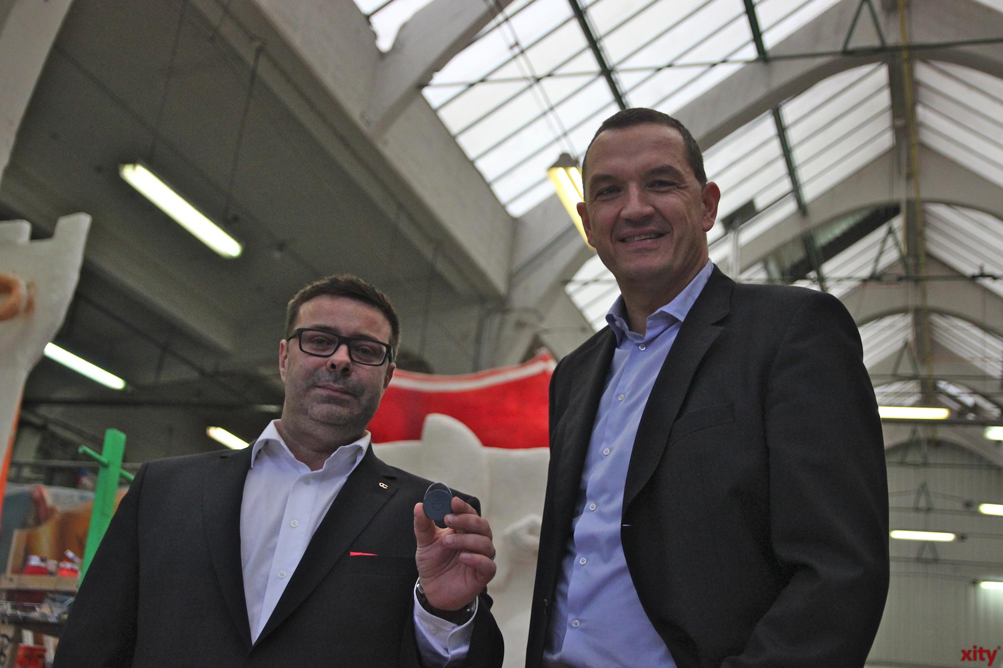 Wagenbauleiter Torsten Langer und Torsten Knopf (Firma Gölzner) mit einem Schließanlagen-Transponder in der Wagenbauhalle (Foto: xity)