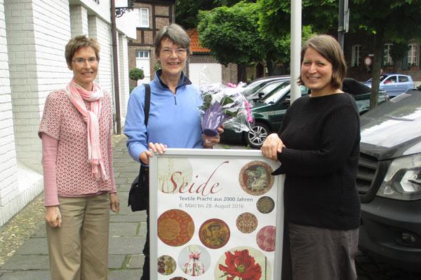 Museumsleiterin Dr. Annette Schieck (rechts) und ihre Stellvertreterin Dr. Isa Fleischmann- Heck (links) konnten nun den 5000sten Besucher der Seide-Ausstellung mit einem  Blumenstrauß begrüßen (Foto: Deutsches Textilmuseum Krefeld)